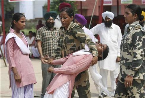 Uma mulher das Forças de Seguranças da Fronteira (BSF) da Índia ensina técnicas de defesa pessoal para alunas de um colégio em Ballaharwal. EFE/Raminder Pal Singh