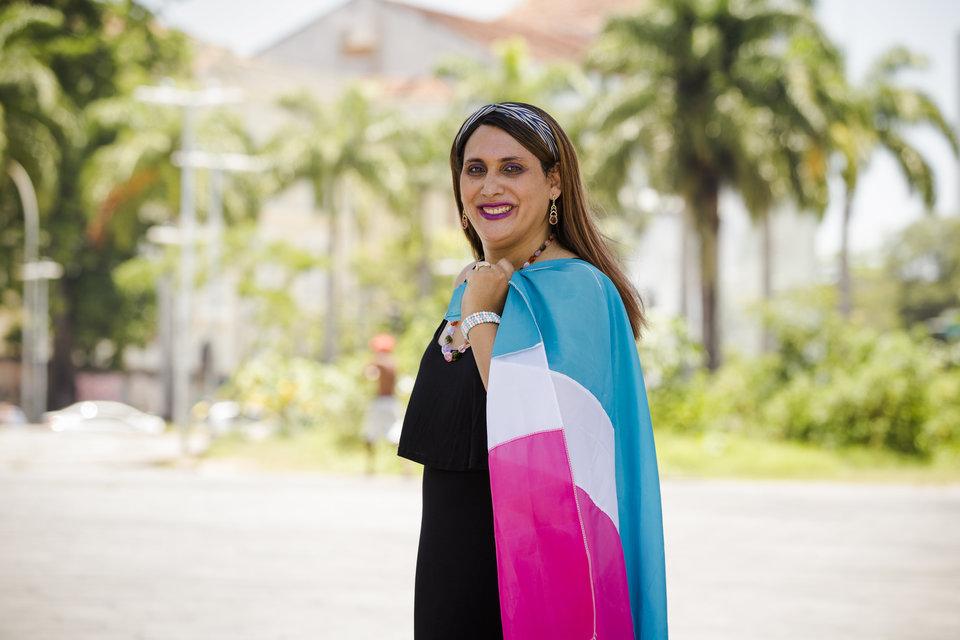 Foto de Maria Eduarda Aguiar com vestido preto e segurando uma bandeira do movimento trans nas cores rosa, branco e azul ao ar livre com árvores ao fundo. Maria Eduarda Aguiar representará a Antra no plenário do Supremo pelo criminalização da homofobia e transfobia. Fim da descrição
